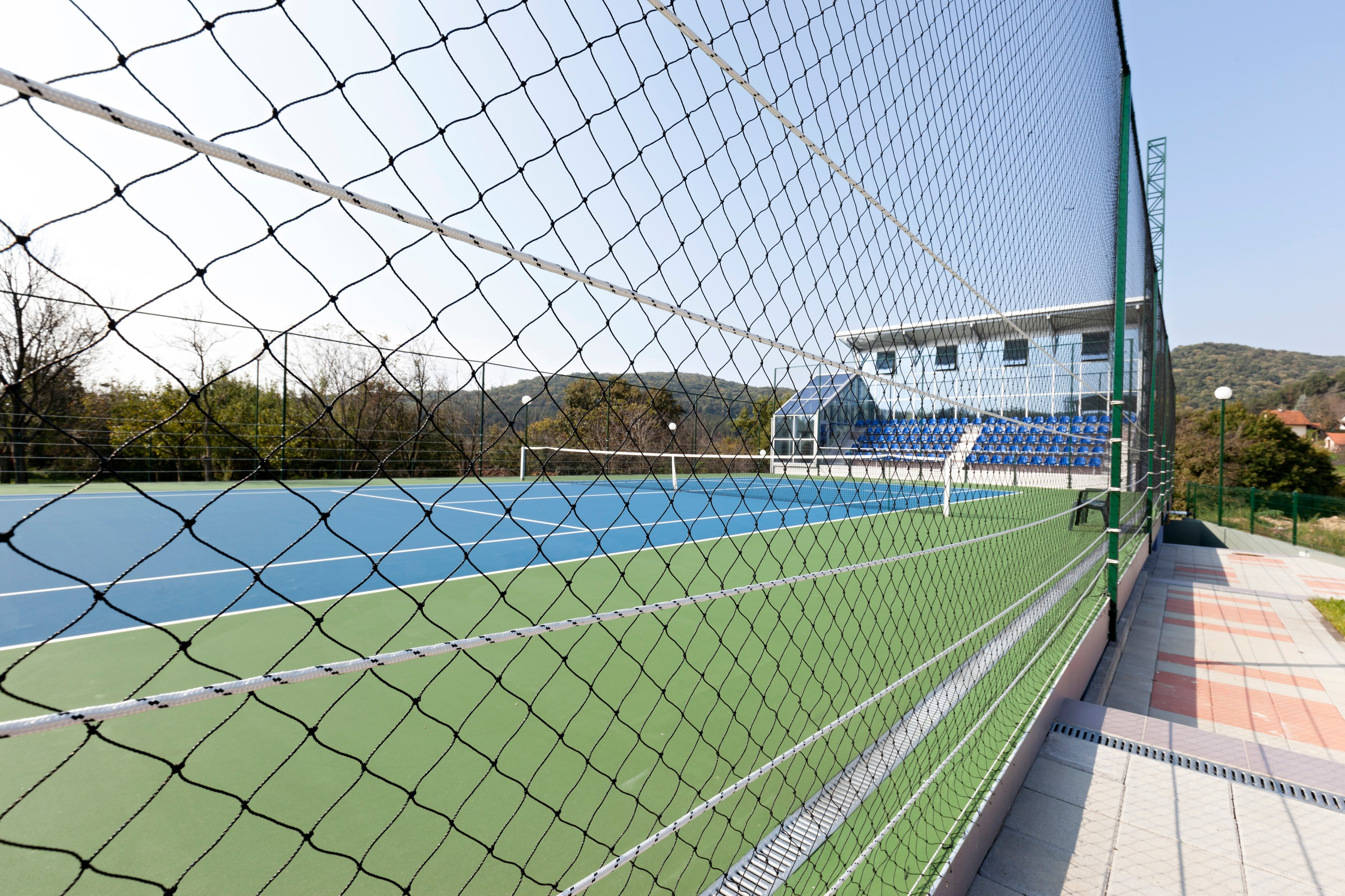 ETC sports Surfaces can finish your acrylic tennis courts with fencing, equipment and floodlighting