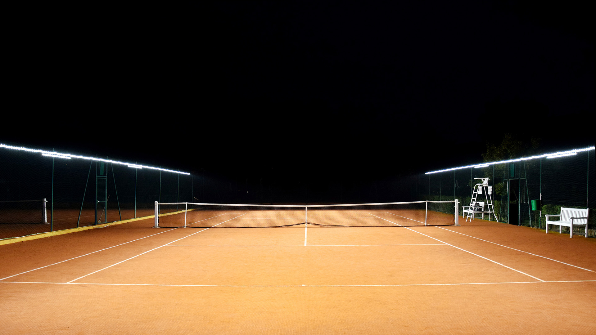 Tennis courts with lights by Tweener® provide optimal playing time at half the cost of traditional column floodlights.